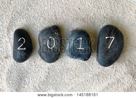 year 2017 writted on black pebbles on sand background