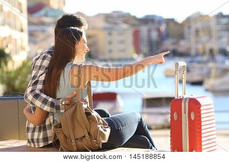 Portrait of couple of tourists with suitcases sitting and cuddling pointing at horizon on vacations in a port of a beach urbanization