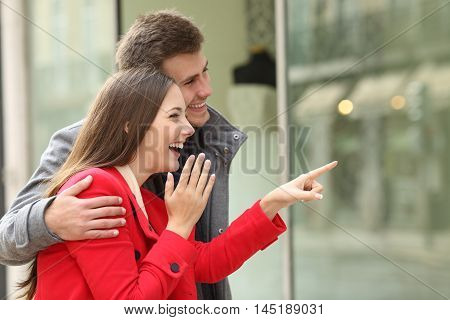 Excited fashion couple shopping and watching in a storefront in a town street