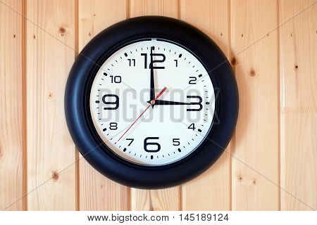 Big round wall clock with a black rim with arrows showing three o'clock hangs on brown wooden wall from vertical planks horizontal view indoor close-up