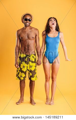 Young beautiful loving couple in beachwear holding hands isolated on the orange background