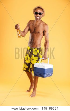 Cheerful young man in hat and sunglasses holding cooler bag and drinking beer over orange background