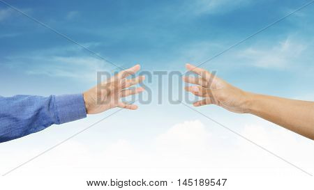 Hands reaching together on blue sky background