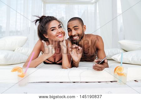 Young smiling happy couple laying on the beach bed and showing okay sign