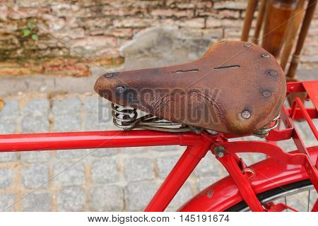Saddle Vintage Red bicycle near the window of old brick wall home background