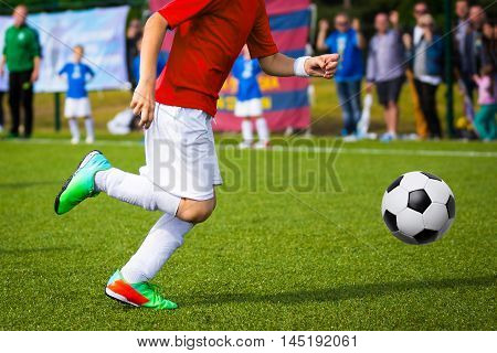 Young soccer player kicking ball on the soccer field