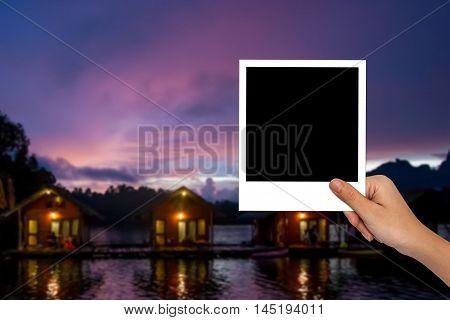 Blank Photo Frame On Female Hand And Blurred Travel Photo