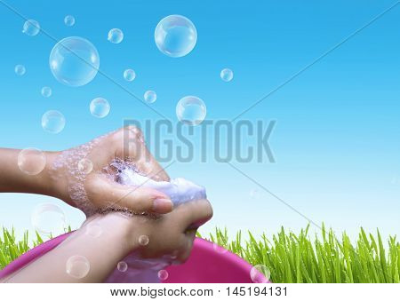 Female Hand Washing Clothes In The Pink Basin With Clear Bubble