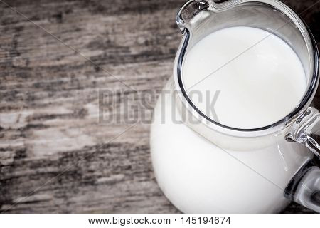 Milk jug full on wooden background view from above closeup.