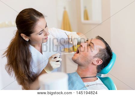 Dentist giving an injection of anesthesia to the patient. Young man at the dental clinic