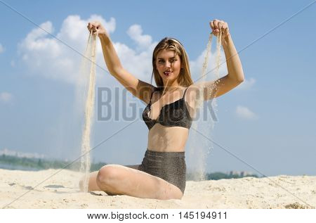 Young and happy model sow the sand trow her hands.