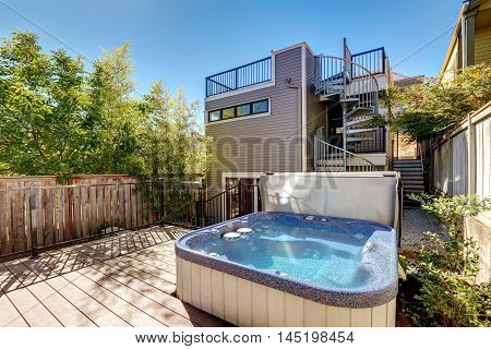 Small Wooden Walkout Deck With Hot Tub. House Exterior.