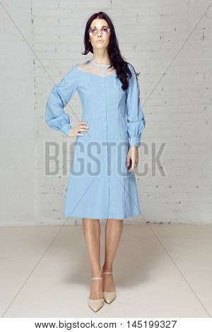 Nymph in pink sunglasses and a blue dress shirt she has black hair. Model in studio with grey bricks wall.