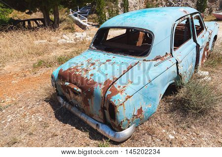 Old abandoned rusted car stands in summer garden rear view