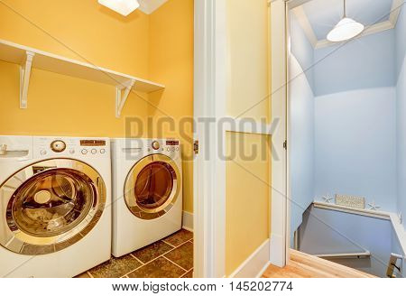 White Modern Appliances In Small Yellow Laundry Room