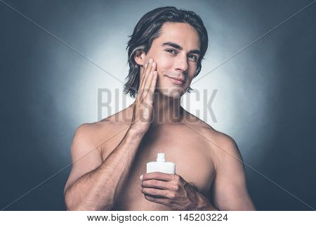 Feeling fresh and clean. Portrait of handsome young shirtless man looking at camera and applying aftershave lotion on face while standing against grey background