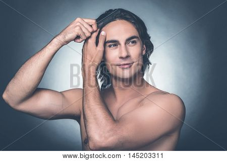 Taking care of his hair. Portrait of young shirtless man combing his hair with hairbrush and looking away while standing against grey background