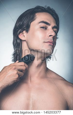 Clean and dry shaving. Handsome young shirtless man shaving with electric razor and looking at camera while standing against grey background