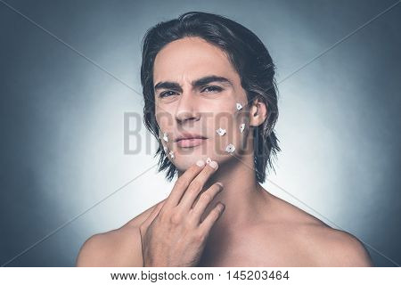 Bad shave. Frustrated young shirtless man touching his face and expressing negativity while standing against grey background