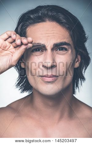 Tweezing eyebrows. Portrait of young shirtless man tweezing eyebrows and expressing negativity while standing against grey background