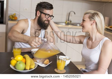 Couple in love sitting at a kitchen table having a breakfast together