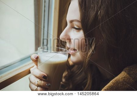 Beautiful Young Woman In Casual Wear Dreaming With Cup Of Hot Coffee Or Tea Over Window