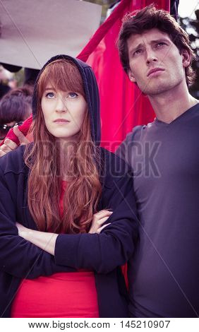 Pessimistic couple participating in a protest standing before a red flag