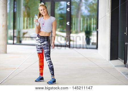Full length portrait of fit smiling woman holding water bottle on footpath