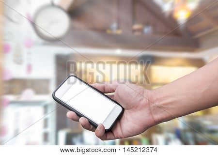 Hand holding smart phone over cafe background