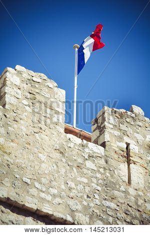 Flag of France flies high up on old building in Riviera town of Antibes