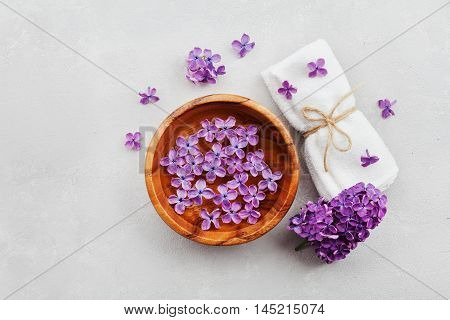 Spa and wellness composition with perfumed lilac flowers, water in wooden bowl and terry towel on gray stone  background. Аromatherapy concept. Top view, flat lay.