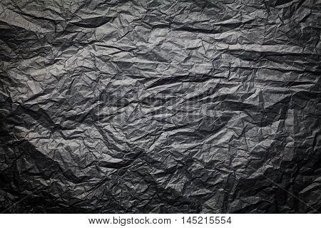 The dark texture of crumpled paper black background.