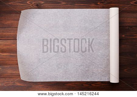 Baking paper background or wallpaper on wooden kitchen table for menu or recipes, top view.