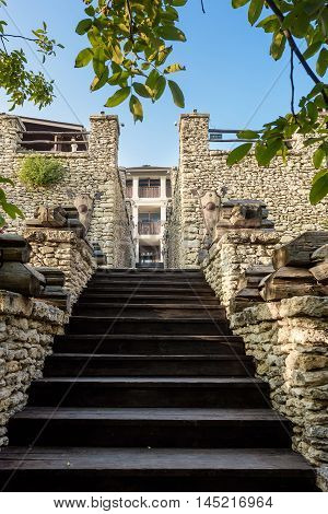 Wooden stairs in a castle with stone walls at orheiul vechi vila etnica in Moldova