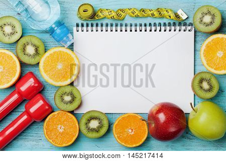 Diet plan, menu or program, tape measure, water, dumbbells and diet food of fresh fruits on blue background. Weight loss and detox concept, top view, flat lay.