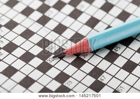 Crossword puzzle and blue pencil. Hobby to improve intellect and erudition.