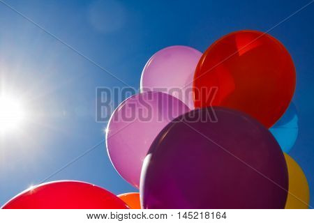 Several colored baloons with blue sky and sun