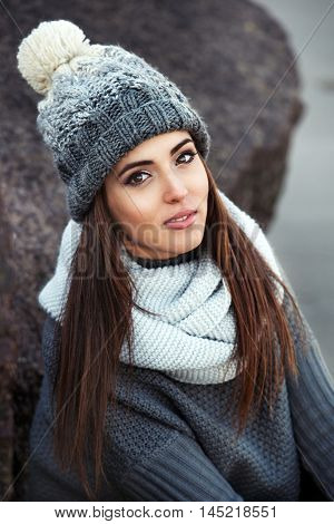 Portrait of beautiful winter woman wearing knitted winter clothes outdoors