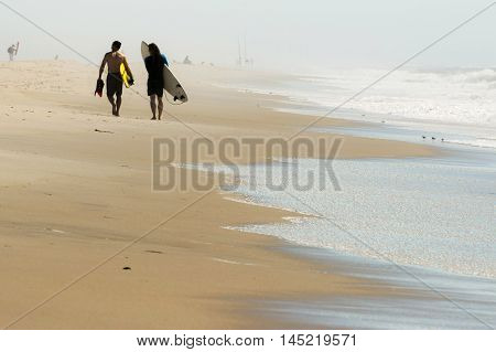 Two surfers walking down the beach on a hazy day