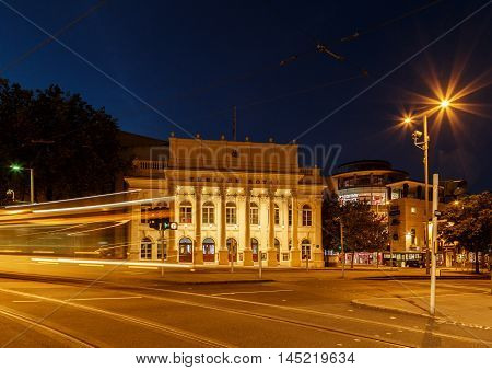 NOTTINGHAM ENGLAND - AUGUST 30: Wide view of the Theatre Royal. Lights of a 'NET' tram are caught as traffic trails. In Nottingham England. On 30th August 2016.