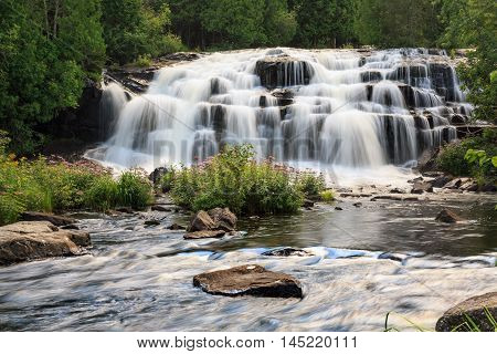 Bond Falls surrounded by wild flowers in the Upper Peninsula of Michigan