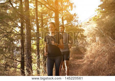 Young Couple Jogging Down A Mountainpath