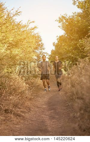 Young Couple Running Down A Path