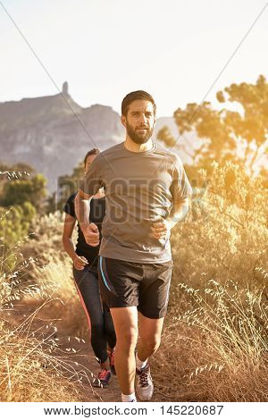 Young Joggers With Mountains Behind Them