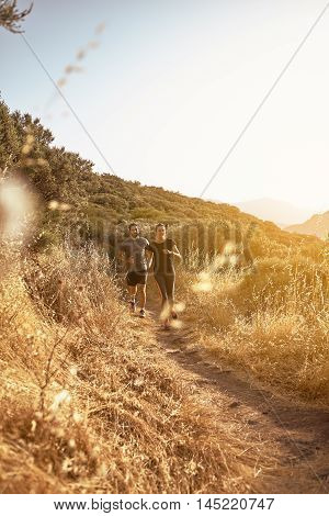 Couple Running Down A Dusty Path