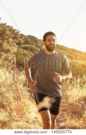 Young Man Jogging Down A Mountain