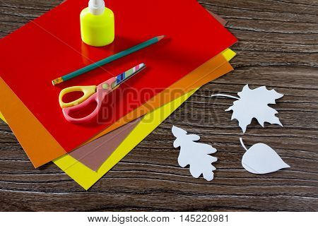Autumn Colored Paper Leaves On The Wooden Background. The Sheet Of Paper Crafts For Kids. Children's