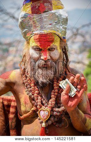 KATHMANDU NEPAL - APRIL 7 2016 : Portrait of Shaiva sadhu (holy man) with traditional painted face in Swayambhunath (monkey temple).