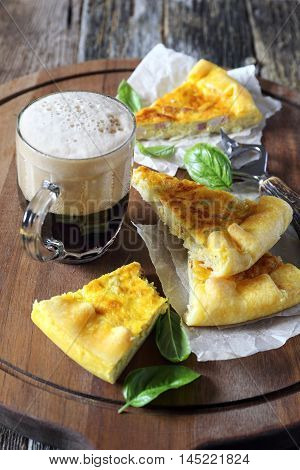 Appetizer: zucchini and lards quiche and mug of dark beer