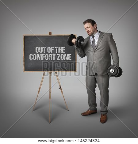 out of the comfort zone text on blackboard with businessman holding weights